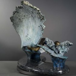 Bronze and glass sculpture of a surfer twisting and turning